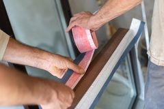 Two man apply special type on window frame. Close up photo of two mature handyman glue protective vapor barrier tape on wood or wooden window frame royalty free stock photography