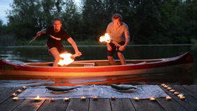 Two man with axe and torch moving on canoe stock footage