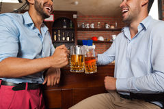 Two Man In Bar Clink Glasses Toasting Sit At Table, Drinking Beer Hold Mugs Close Up Stock Photo