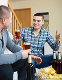 Two man with beer sit and talk. Two happy old friends with beer during weekend royalty free stock photography