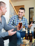 Two man with beer sit and talk Royalty Free Stock Photos