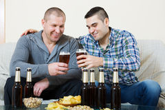 Two man with beer sit and talk. Young men drinks beer with old friend at home royalty free stock photography
