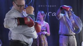 Two man in boxing gloves swaddle baby doll on stage in restaurant. Contest. People. Family stock video footage