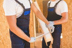 Two man building wooden house. Two young man building wooden house. Ecology concept Stock Image