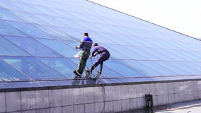 Two man cleaning the windows on a building