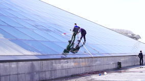 Two man cleaning the windows on a building. We make your windows look crystal clear stock video