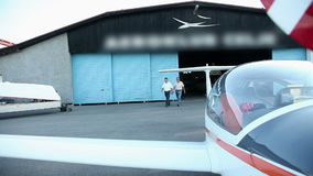 Two man coming from hangar ready for flight. Small airport with beautiful landscape where planes are taking off. Shots from outside, inside plane cabin and stock video footage