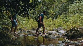 two man crossing a small river in the rainforest jungle royalty free stock images