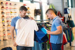 Two man deciding on new sportswear. Two men deciding on new sportswear in sports store Royalty Free Stock Photography