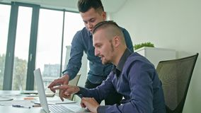 Two Man Discussing Ideas Using Laptop. Two Man in modern start up office male team leader pointing at screen discussing diverse people group teamwork using stock footage
