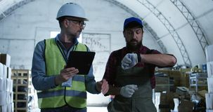 Two man discussing in a warehouse. Medium shot of two man discussing in a warehouse stock footage