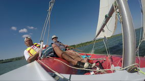 Two man drive a sport sailing yacht. Close-up view of the cockpit stock footage