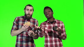 Two man eating burgers. Two multiracial men eating black and white hamburgers, one a bearded Caucasian and the other a young black guy, upper body isolated on stock footage