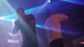Two man exhale steam from electronic cigarette. Vapers. Contest in nightclub. Spotlights. Slow motion stock footage