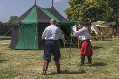 Two Man fight in medieval costume. In Krakow at the time of the fair on the occasion of the feast of Saint John. They train to fight on the Vistula near Wawel Royalty Free Stock Photos