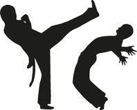 Two man fighting capoeira. Silhouettes Stock Photos