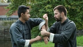 Two man fighting at training in traditional wear. Two serious warrior focused attention at practicing kung fu skills for self-defense in park. Master moving and stock video