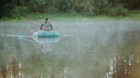 Two man fishing on the rubber boat in the forest lake. Beautiful morning landscape, dawn and fog above the water. stock footage