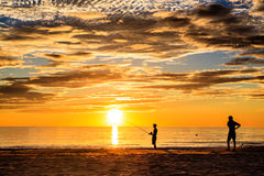 Two man fishing in surf royalty free stock photo