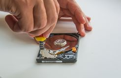 Two man hands fixing harddisc using screwdriver, close-up Royalty Free Stock Photography