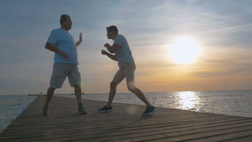 Two man having boxing training on the pier. Slow moion of young and mature man having boxing workout on the pier at sunset. Checking the reaction stock footage