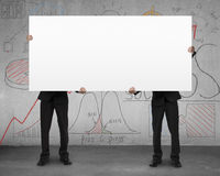 Two man holding board with business doodles on wall Stock Photography