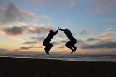 Two man jump hight in front of sea sunset Stock Photos