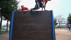 Two man jumping over high obstacle. Slow motion of two man jumping over high obstacle as part of a game stock video