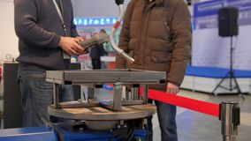Two man looking to robotics arm for technowelding on industrial exhibition. Close up stock footage