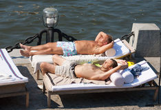 Two man lying on couches and sunbathing at Olive Beach Stock Images
