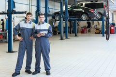 Two man mechanics working. Two men mechanics working in car repair service Royalty Free Stock Photography