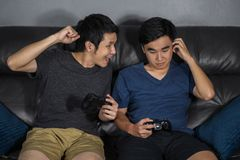 Two man playing video games while sitting on sofa. win and lose royalty free stock image