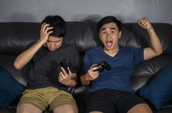 Two man playing video games while sitting on sofa. win and lose stock photography
