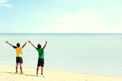 Two man raised arm on the beach Stock Photos