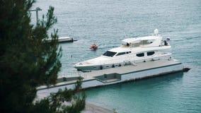 Two man ride jet ski along white motor yacht to pier on ocean side, summer day stock video