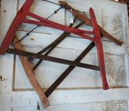Two-man saws for sale in antique shop, cross cut, buck saws, wooden handles. Two antique cross cut buck saws on display, hanging on a dirty door, for sale at royalty free stock images