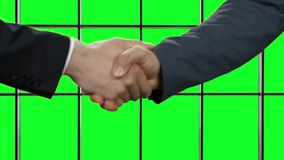 Two man shaking hands. Two man shaking hands on green background. It's a deal. Remember your promises. Respect and approval stock footage
