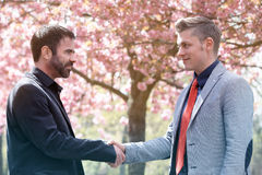 Two man shaking hands outdoors Stock Image