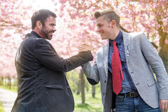 Two man shaking hands outdoors Stock Photo