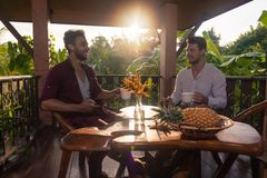 Two Man Sitting On Summer Terrace Hold Cup Having Breakfast Talking, Guys In Morning Drinking Coffee Outdoors. With View On Tropical Forest Stock Images