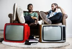 Two man sitting and two retro television. Two men sitting and two retro television Stock Images