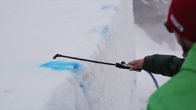 Two man spay blue dye on snowy slope on ski resort. Mountains. Marking. Sport. Two man spay bright blue dye on snowy slope on ski resort. Mountains. Marking stock video