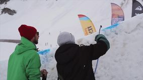 Two man spay blue dye on snowy slope on ski resort. Snowy mountains. Marking. Sport stock footage