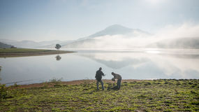 Two man stand by lake anh Alone tree on the lake, sunrise at the mountai, foggy, cloud on the sky Royalty Free Stock Photos