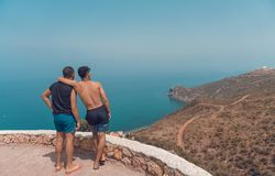 Two Man Standing on Mountain Cliff With Ocean View stock photo