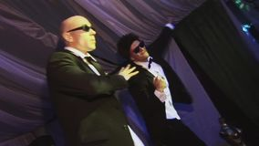 Two man in sunglasses dance in dinner jackets on stage of nightclub. Spotlights. Dancers. Movements stock video footage