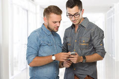 Two man talking about  mobile phone. Portrait of two young men talking about  mobile phone Royalty Free Stock Photo