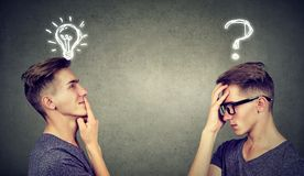 Two men thinking one has a question another solution with light bulb above head. Two man thinking one has a question another solution with light bulb above head Royalty Free Stock Image