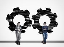 Two man using phone against a white wall painted with engine gear mechanism. royalty free stock images