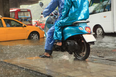 Two man wearing raincoat riding motorcycle Royalty Free Stock Photo